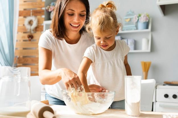 小さな女の子と彼女の母親が生地を準備