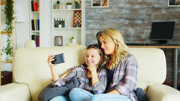 어린 소녀와 그녀의 어머니는 전화로 화상 통화를 하는 동안 거실 소파에 앉아 있습니다.