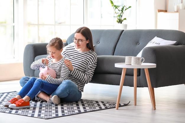 自宅で教育のための貯蓄を持つ少女と彼女の母親