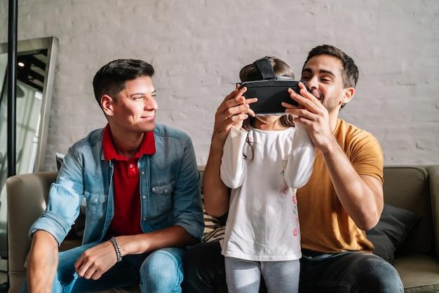 小さな女の子と彼女の両親は、自宅でvrメガネを使ってビデオゲームをプレイしています。家族の概念。