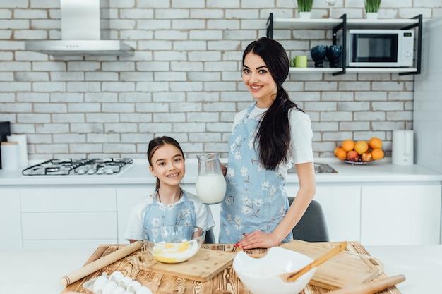 Маленькая девочка и ее сестра готовит домашнюю еду.