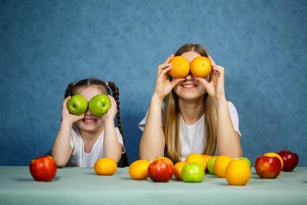 어린 소녀와 엄마는 과일을 가지고 놀고 장난을 칩니다. 그들은 티셔츠를 입고 있다