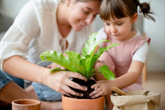 집에서 식물을 화분에 심는 어린 소녀와 엄마