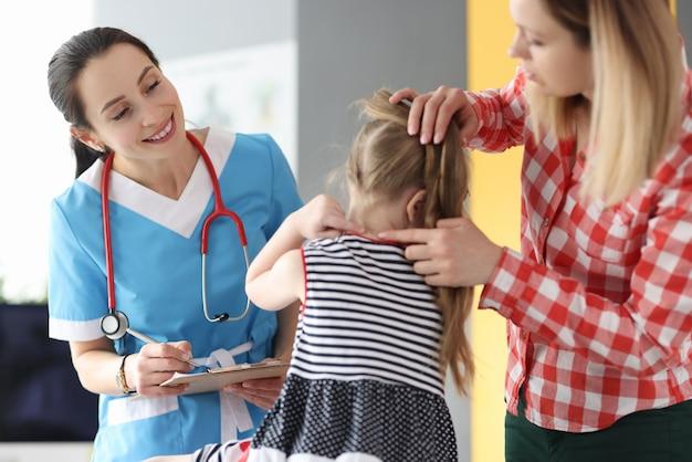 의사에게 아픈 목을 보여주는 어린 소녀와 엄마