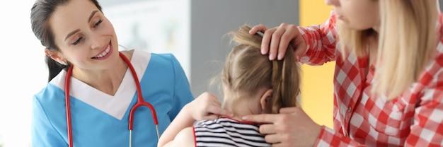 小さな女の子とお母さんが医者に首の痛みを示しています