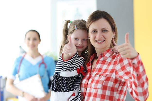 의사 약속에 엄지 손가락을 보여주는 어린 소녀와 엄마