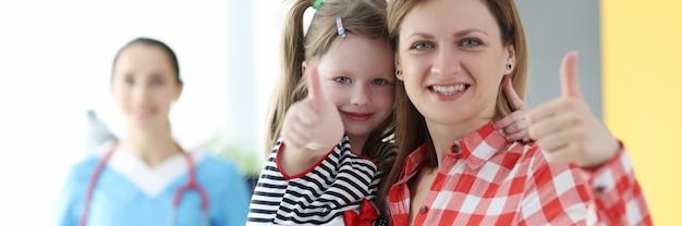 医者の予約で親指を表示する小さな女の子とお母さん
