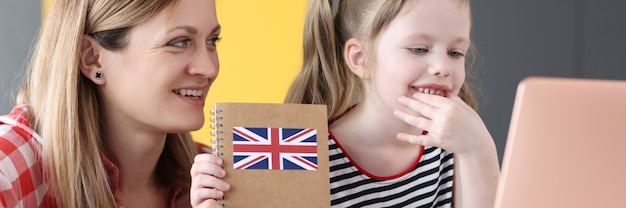 英語の教科書とラップトップの前に座っている小さな女の子とお母さん