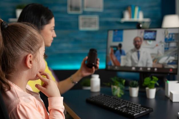 Маленькая девочка и мама с помощью телемедицины для консультации с врачом дома. семья узнает о медицинской диагностике и медицине с помощью видеозвонков и технологий онлайн-конференций