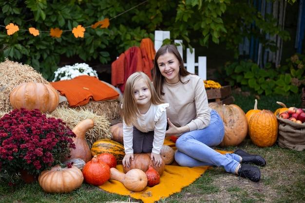 Маленькая девочка и мать наслаждаются празднованием урожая на тыквенном участке