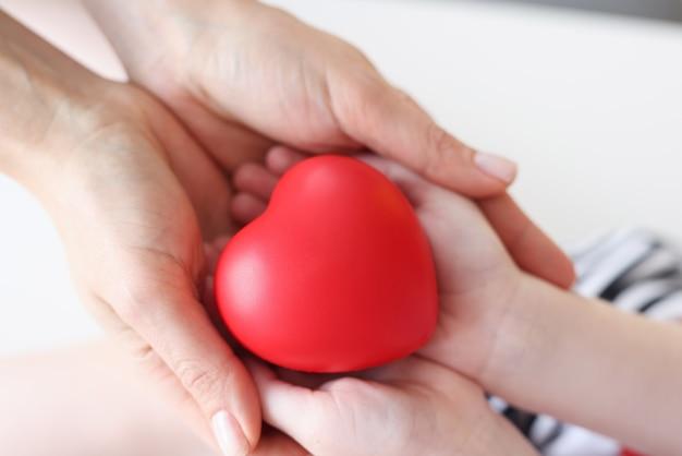 Маленькая девочка и мать руки держат красное игрушечное сердце крупным планом