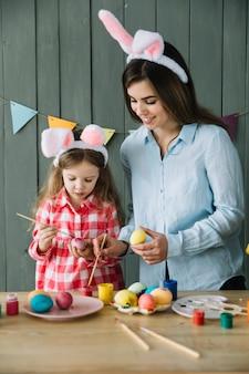 Маленькая девочка и мать в ушах зайчика рисуют яйца на пасху