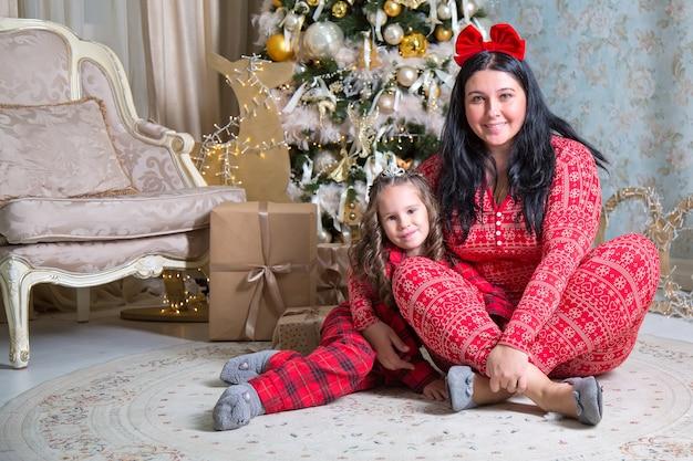 贈り物やクリスマスツリーの近くの小さな女の子と母親。