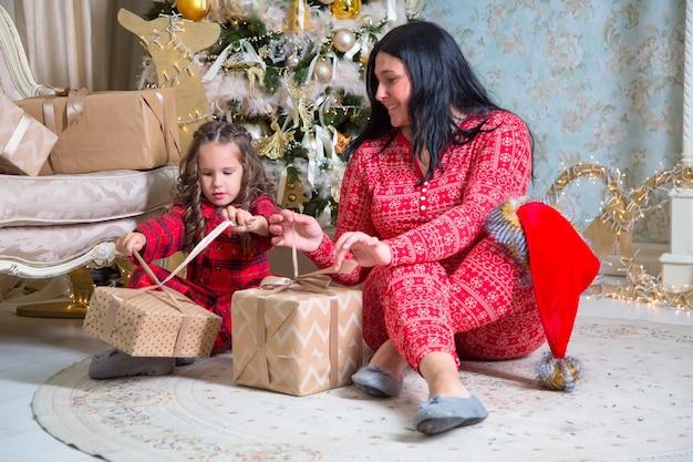 小さな女の子と母親がクリスマスツリーの近くで贈り物を開きます。