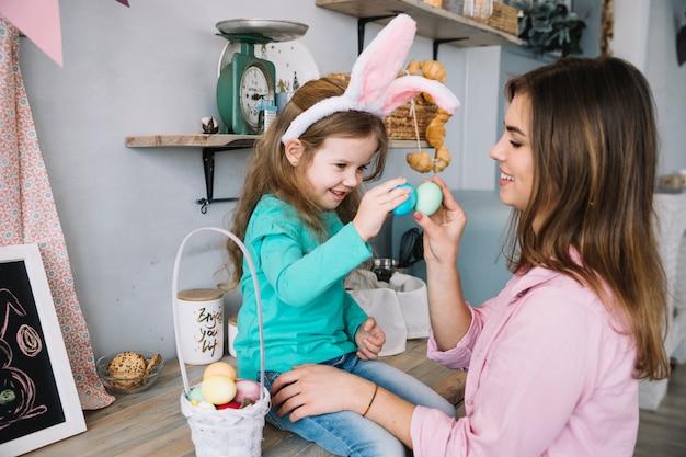 小さな女の子とイースターエッグと遊ぶ母
