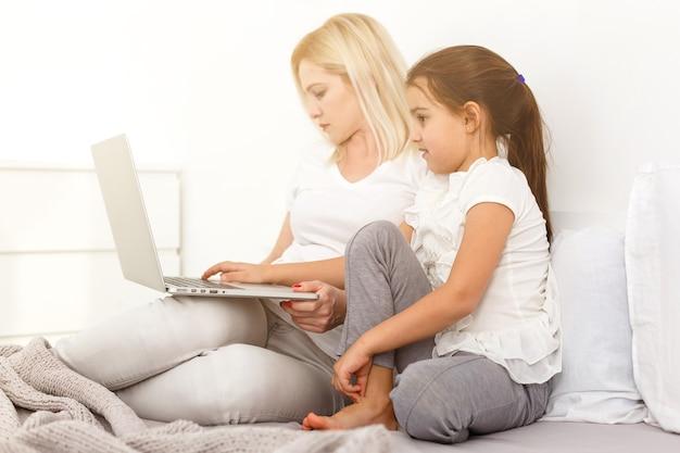 침대에 노트북과 어린 소녀와 어머니