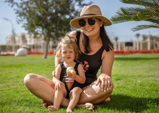 Маленькая девочка и матери летом на траве среди пальм.