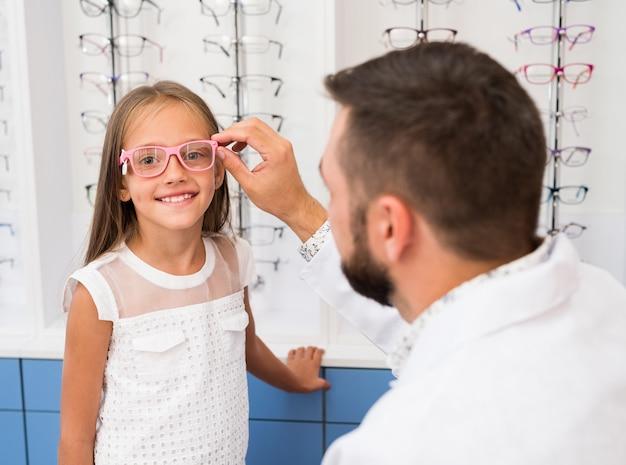 Маленькая девочка и офтальмолог, выбирая очки