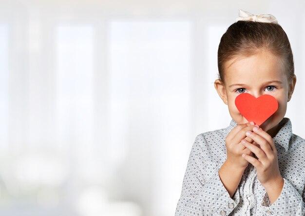 小さな女の子と赤い心。