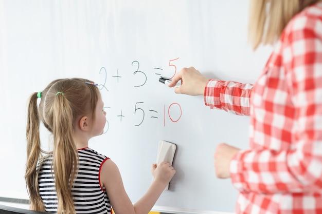 어린 소녀와 교사가 칠판에 수학 방정식을 해결
