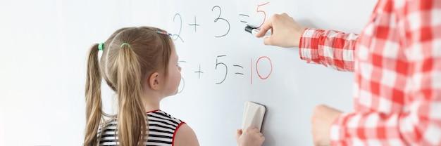 Маленькая девочка и учитель, решающие математические уравнения на доске