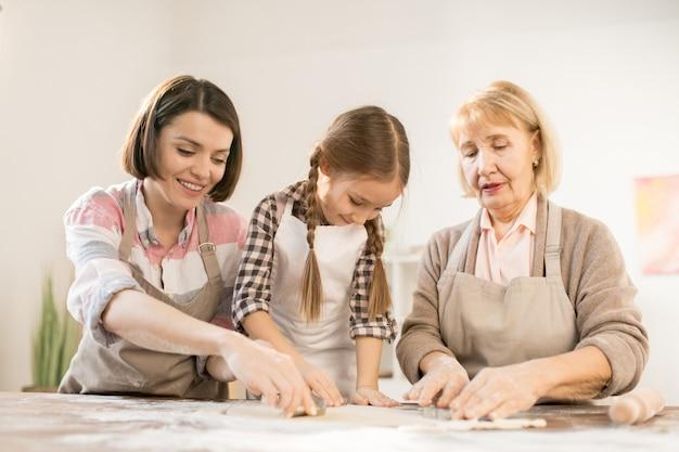 Маленькая девочка и две женщины в фартуках, используя формочки для печенья во время приготовления домашней выпечки