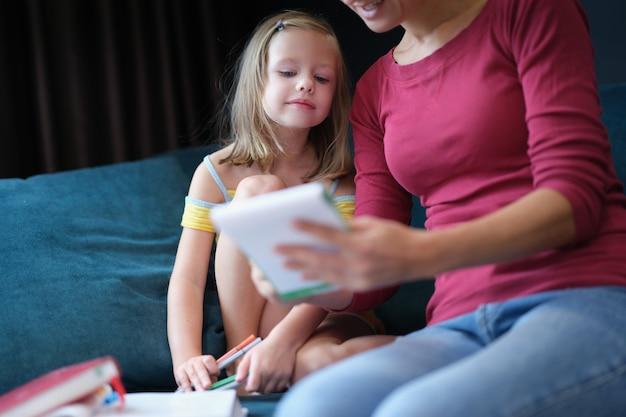 교과서와 함께 소파에 앉아 어린 소녀와 여자