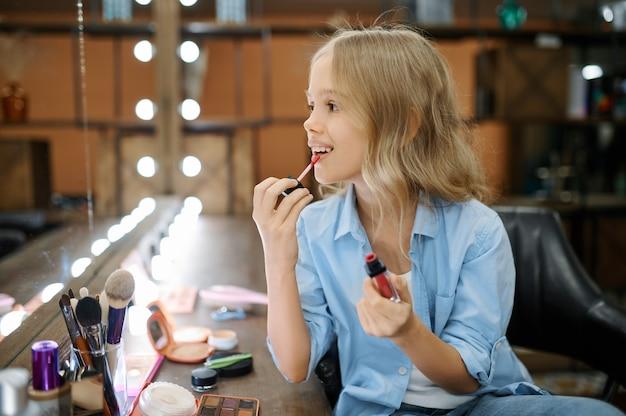 어린 소녀는 메이크업 살롱에서 거울에 립스틱을 적용