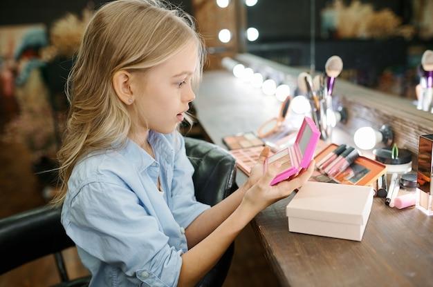 어린 소녀는 메이크업 살롱에서 거울에 포마드를 적용