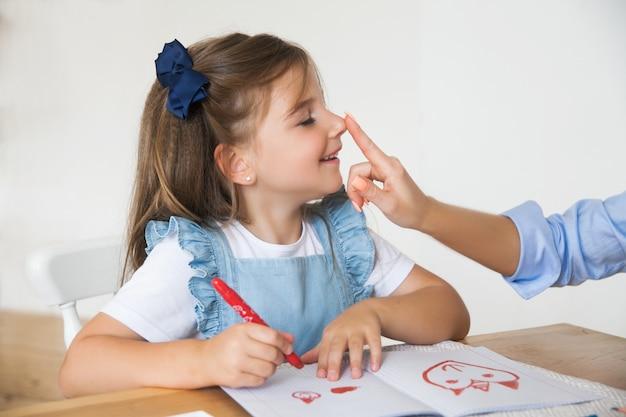 少女は学校の準備をしており、鉛筆と絵の具で描くことに取り組んでいます