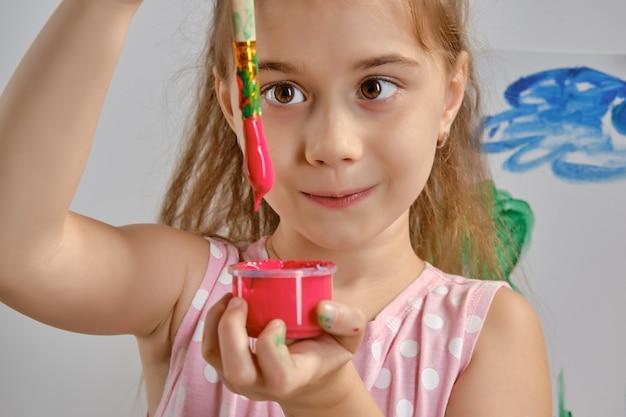 Маленькая девочка-художник в розовом платье стоит за мольбертом и рисует кистью на холсте