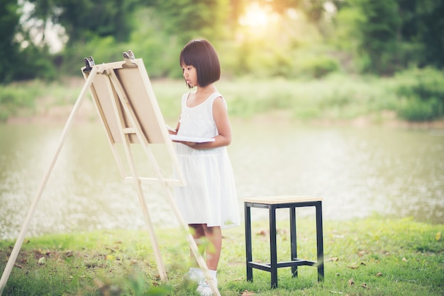 Little girl artist painting picture in the park
