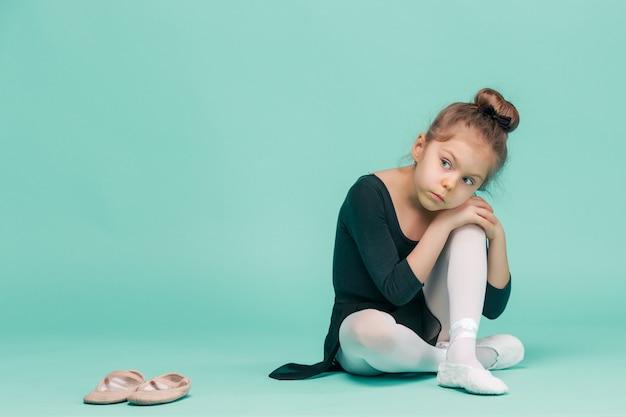 The little girl as balerina dancer sitting on white wooden chair at blue studio