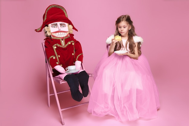 A little girl as beauty ballerina at pink long dress with nutcracker at pink studio with cup of tea