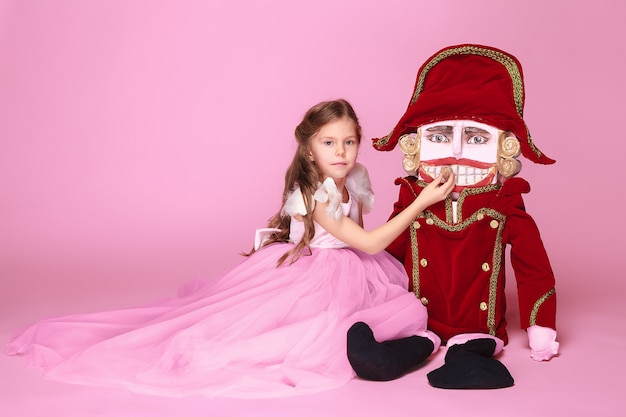 A little girl as beauty ballerina at pink long dress with nutcracker at pink studio