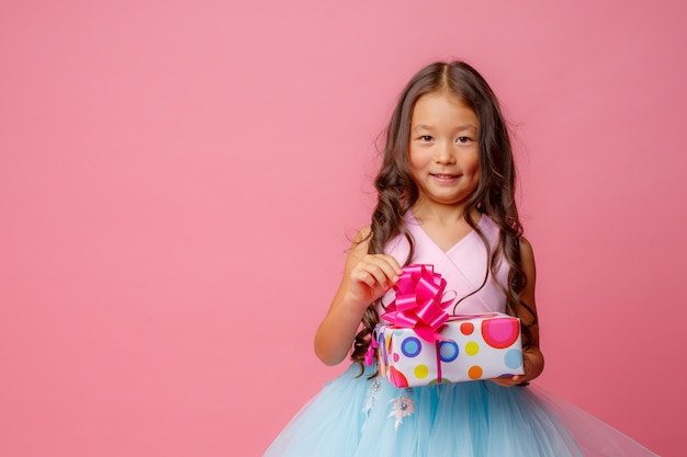 A little girl of asian appearance holds a gift in her hands celebrating her birthday