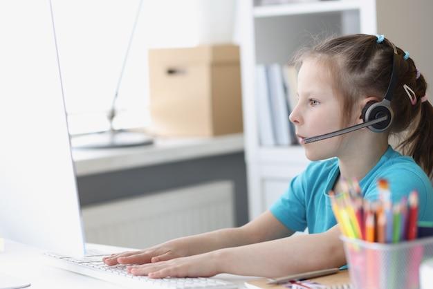 マイク付きヘッドフォンでコンピューターの小さな女の子がコンピューターで動作します