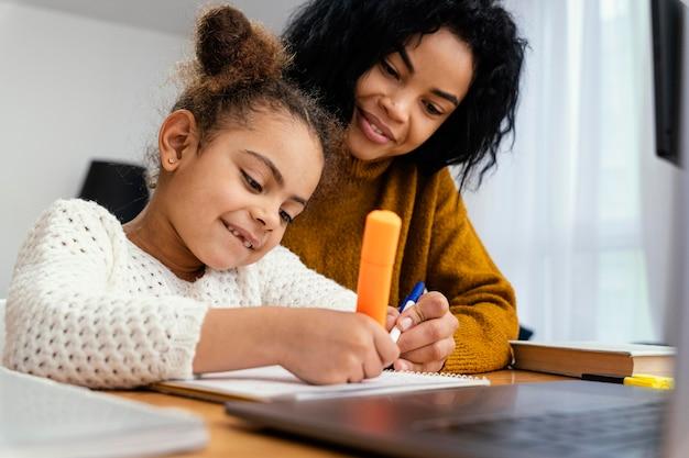 彼女の姉から助けを得ているオンライン学校の間に家にいる小さな女の子