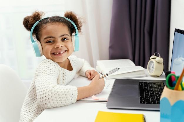 ノートパソコンとヘッドフォンでオンライン学校の間に家にいる小さな女の子