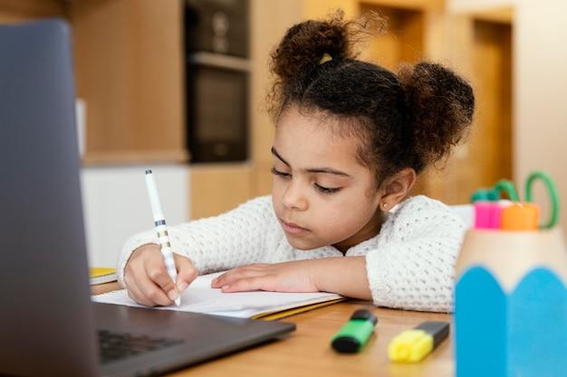 노트북으로 온라인 학교 동안 집에서 어린 소녀