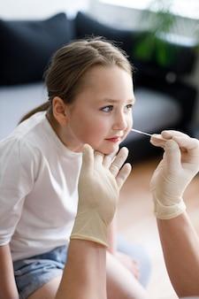 코 비드 -19를 보여주는 호흡기 바이러스 검사 절차를 수행하는 코에서 비강 점액 검사 샘플을 채취하는 동안 집에서 어린 소녀