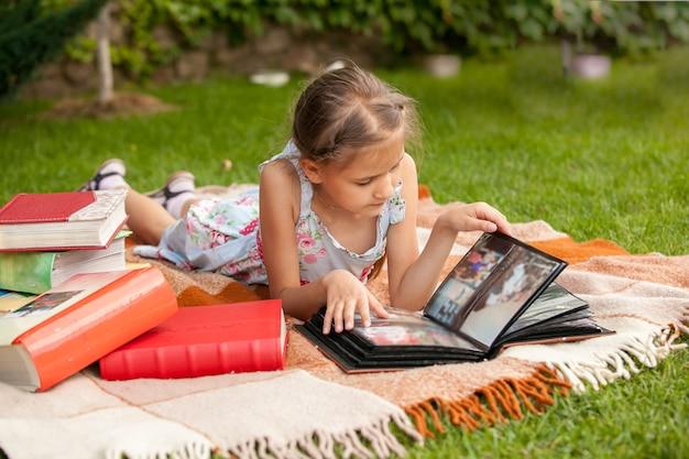 Маленькая девочка в парке, глядя на семейный фотоальбом