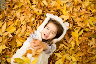 Little girl at the autumn leaves
