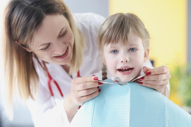 Маленькая девочка в офисе дантиста. лечение молочных зубов у детей