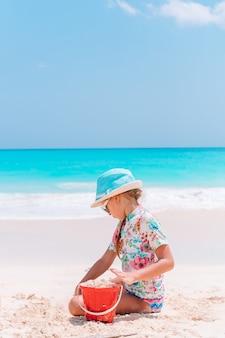 여름 휴가에 모래성을 만드는 열 대 해변에서 어린 소녀