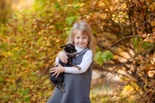 Little girl in autumn in the park holding a small dog smiles