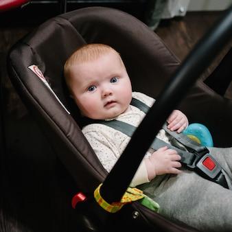 おもちゃで遊んでいる小さな女の子の赤ちゃん、幼児は車の座席に横たわって微笑んでいます。フラットレイ、上面図。テキスト用のスペースをコピーします。小さな女の赤ちゃん、コンセプト幸せな家族、ライフスタイル。旅行や旅行の準備。