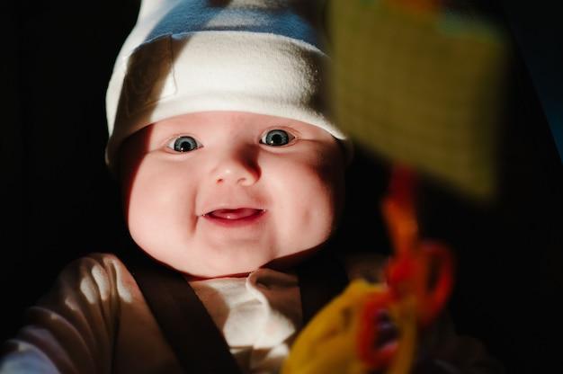 おもちゃで遊んでいる小さな女の子の赤ちゃん、幼児は車の座席に横たわって微笑んでいます。旅行や旅行の準備。フラットレイ、上面図。テキスト用のスペースをコピーします。チャイルドシートの道路での安全。