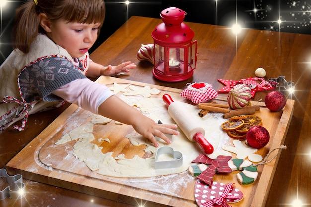 クッキーカッターでペストリーを切るクリスマスクッキーを焼く少女