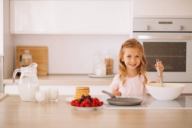 Little girl baking pancakes at the kitchen